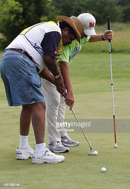 Golf coach Glenn Paulus assists visually impared military veteran Wilber Eugene with a fareway shot during the golf competition at the National...