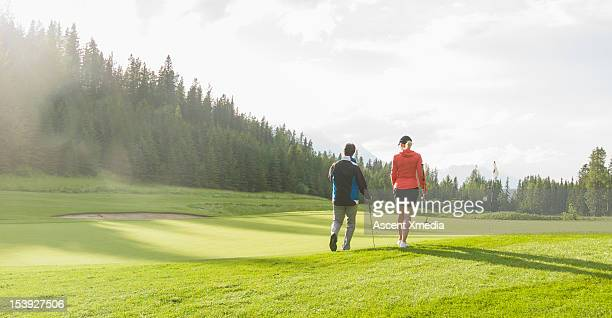 Golf couple walk onto green at sunrise, mtns