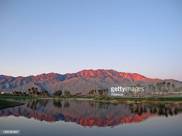 golfplatz im morgengrauen mit sunrise kissed mountains - palm springs stock-fotos und bilder