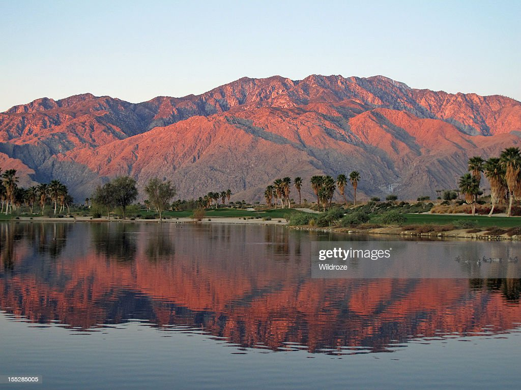 Golf course at dawn with sunrise kissed mountains : Stock Photo