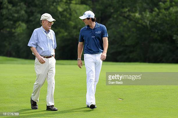 Golf course designer Peter Dye and Rory McIlroy of Northern Ireland walk along the seventh fairway during the ProAm round for the BMW Championship at...