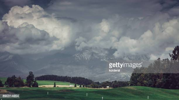 golf course with mountains covered by clouds on background - golf tournament stock pictures, royalty-free photos & images
