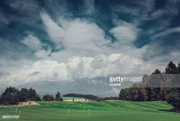 Golf course with mountains covered by clouds on background