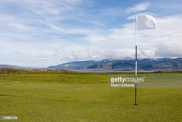 golf course with mountains in the background - golf flag stock photos and pictures