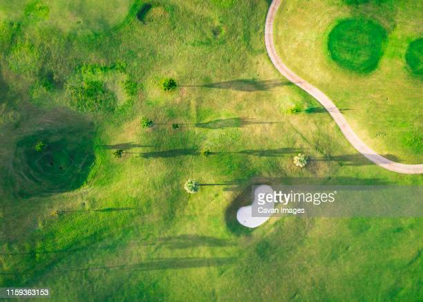 a golf course with trees and shadows from above - bermuda stock pictures, royalty-free photos & images