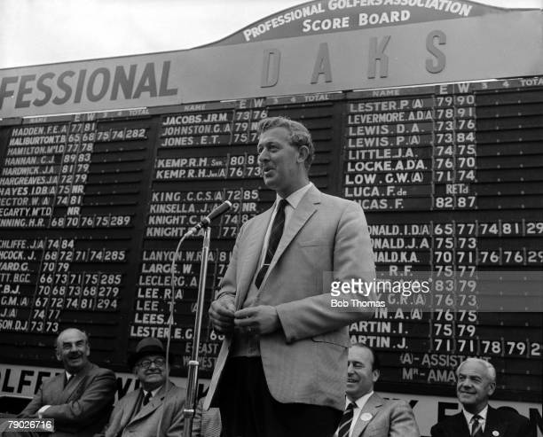 Bernard Hunt stands in front of the scoreboard and speaks to the crowds with the aid of a microphone