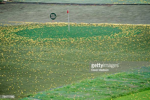 golf driving range with green and pin surrounded by golfballs - driving range stock pictures, royalty-free photos & images