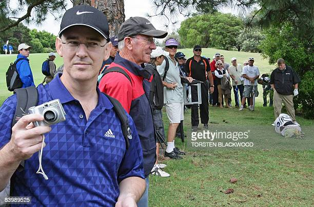 Golf fan Brad Clegg displays his camera after it was smashed against a tree by controversial American golfer John Daly during the opening round of...