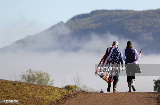 A golf fan draped in the US flag walks between holes during the Session 4 Singles games on the final day of the 2010 Ryder Cup golf competition...