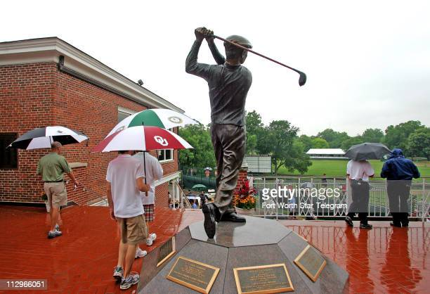 Golf fans deal with the rain near a statue of golf legend Ben Hogan during the second round of the Crown Plaza Invitational at Colonial Friday May 25...