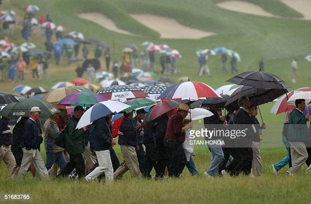 Golf fans follow the action in a driving rain during the second round of the 102nd US Open Championship 14 June, 2002 at Bethpage State Park in...