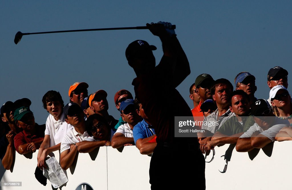Golf fans look on as Tiger Woods watches his tee shot on the 17th hole during the final round of the BMW Championship held at Cog Hill Golf & CC on September 13, 2009 in Lemont, Illinois.