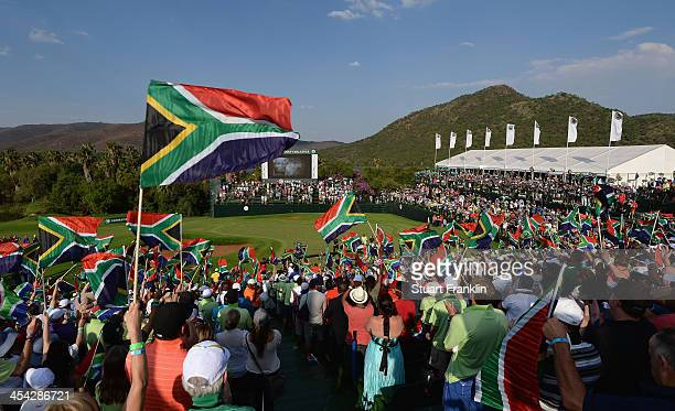 Golf fans wave South African flags in tribute to the late President Nelson Mandela after the final round of the Nedbank Golf Challenge at Gary Player...