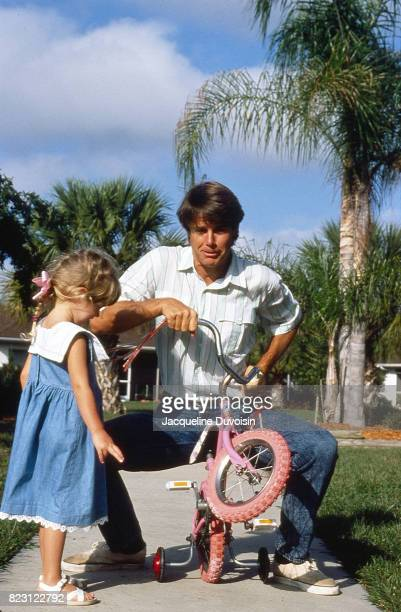 Feature Portrait of Paul Azinger with his daughter while seated on her bicycle during photo shoot outside his home Bradenton FL CREDIT Jacqueline...