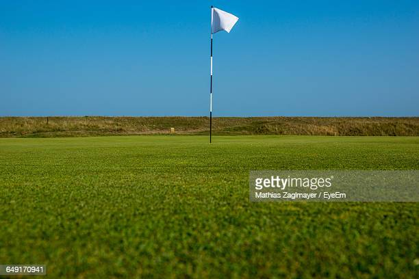Golf Flag On Grassy Field Against Clear Blue Sky