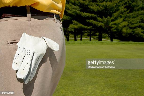 Golf glove hanging out of man's pocket
