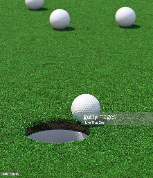 Golf hole with a ball about to fall in