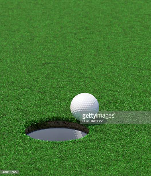 golf hole with a ball about to fall in - green golf course stock pictures, royalty-free photos & images