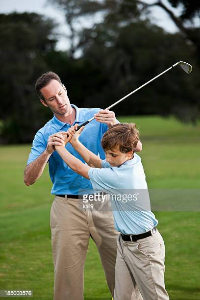 golf instructor adjusting boy's grip - sport venue stock pictures, royalty-free photos & images