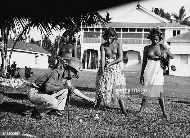 A golf instructor adjusts the putter for a young Pacific Island girl as she learns to play golf