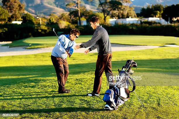 Golf lesson: young coach correcting golfer's swing