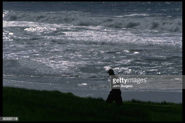 Pebble beach Pro Am Silhouette of Tiger Woods walking alone on the beach