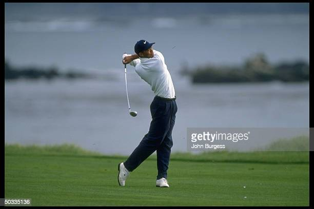 Pebble beach Pro Am. Tiger Woods in action alone, driving during tournament.