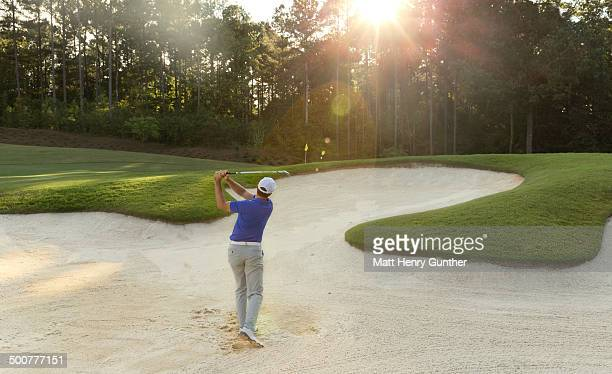 golf player hitting ball out of sand trap - sand trap stock pictures, royalty-free photos & images