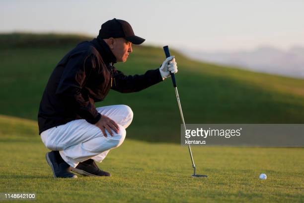 jogador de golfe que olha ao furo para decidir no tiro-golfe das ligações - putting - fotografias e filmes do acervo