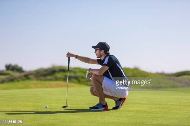 golf player looking to hole for deciding on the shot - links golf - meter unit of length stock pictures, royalty-free photos & images