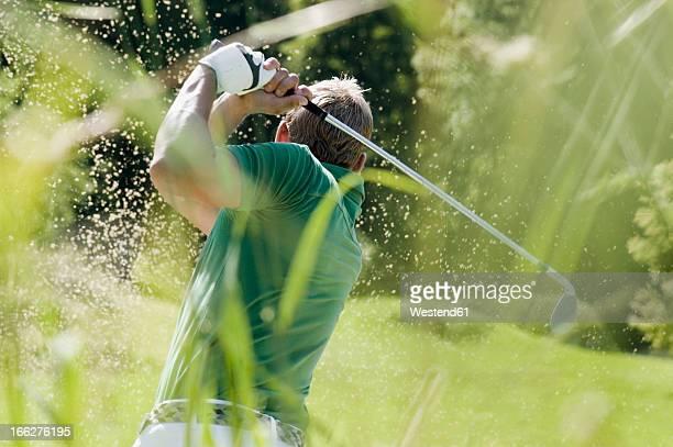 golf player, rear view - golfschwung stock-fotos und bilder