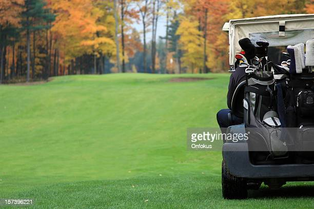Golf Player Riding in Golf Cart Towards Putting Green