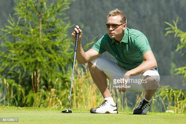 Golf player squatting on golf course, looking away