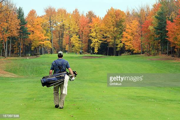 Golf Player Walking Towards the Putting Green in Autumn