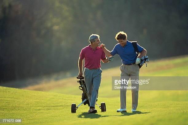 Golf, players walking on fairway