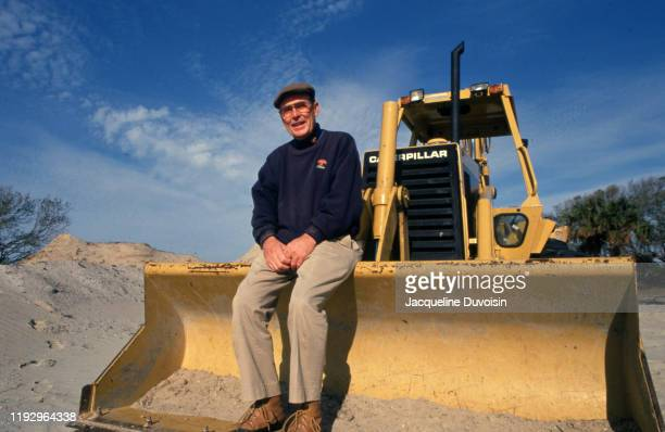 Portrait of course architect and designer Pete Dye seated on bulldozer equipment during photo shoot on construction site that will become The Ocean...