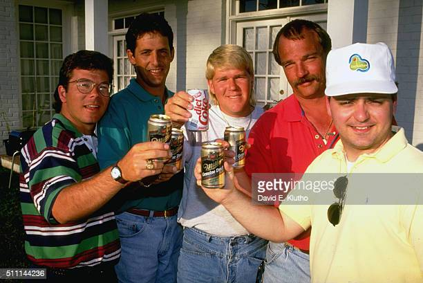 Portrait of Sean Pacetti caddie Greg Rita John Daly Blake Allison and Chuck Hughes toasting cans and posing for photograph Daly holding soda while...