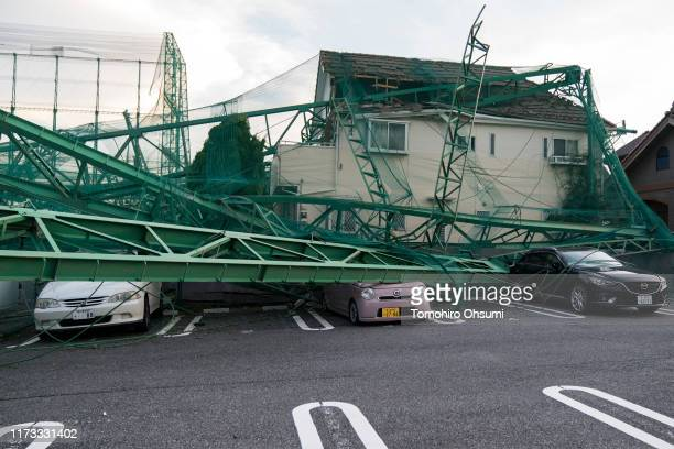 Golf practice range fences collapsed to a house and vehicles are seen following the passage of Typhoon Faxai on September 09, 2019 in Ichihara,...