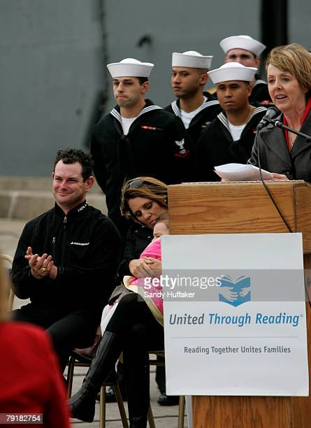Golf pro Rory Sabbatini applauds with his wife Amy after presenting a check for $170000 to the United Through Reading Military program at the 32nd...
