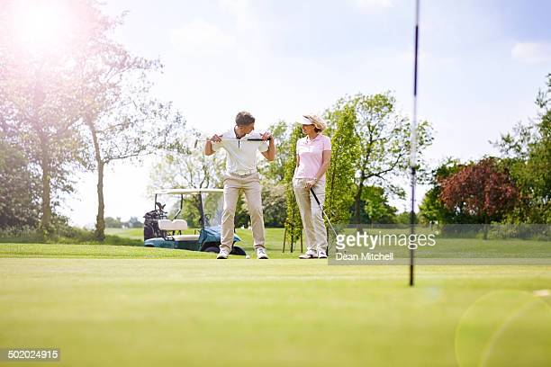 Golf pro teaching female golfer on her stance