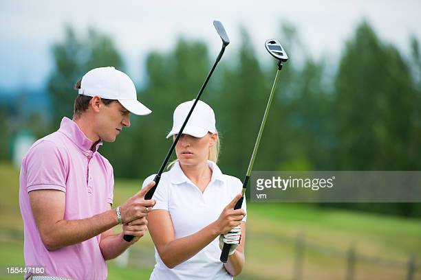 golf pro teaching female golfer - driving range stock photos and pictures