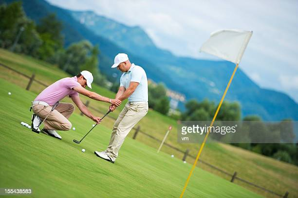 golf pro teaching male golfer - putting stock photos and pictures