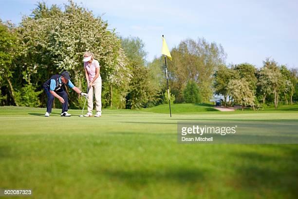 Golf pro teaching the proper putting technique