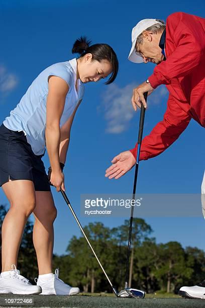 Golf pro teaching young female golfer