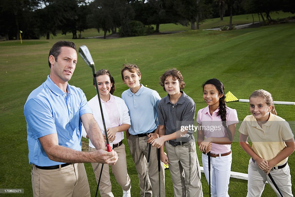 Golf pro with group of children on driving range : Stock Photo