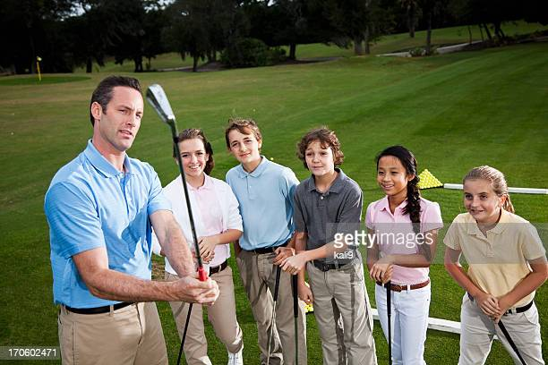 Golf pro with group of children on driving range