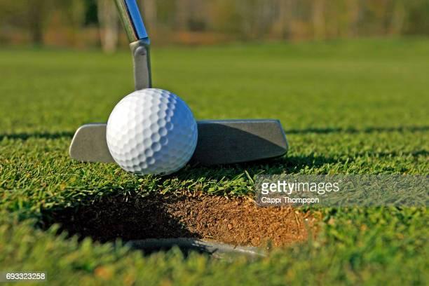golf putter close up with ball - einlochen golf stock-fotos und bilder