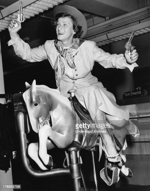 Golf star Babe Didrikson has fun with sidesaddle and pistols on a mechanical horse New Orleans Louisiana c 1952