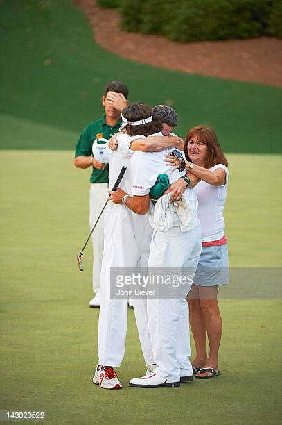 Bubba Watson victorious, hugging caddie Ted Scott on No 10 after winning tournament during Sunday playoff at Augusta National. View of Molly Marie...
