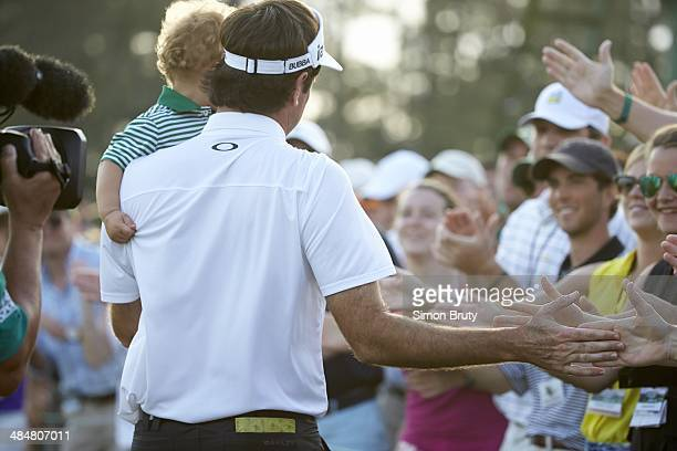 The Masters Rear view of Bubba Watson victorious with fans while holding his son Caleb Watson at No 18 hole after winning tournament on Sunday at...